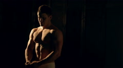 Muscular man bodybuilder. Man posing on a black background, shows his muscles Stock Footage