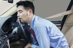 Businessperson sleeping in the car - stock photo