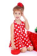 Beautiful girl in a red summer dress with polka dots near the gi - stock photo