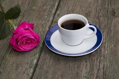 Cup of coffee on an old table and nearby a rose Stock Photos