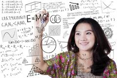 Girl writes math and science formula Stock Photos