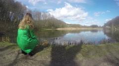 Blond woman with green coat feeding duck birds near lake. 4K Stock Footage