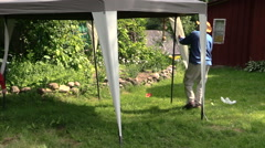 People build tent bower in garden near rural homestead house Stock Footage