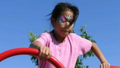 Cute Asian Girl With Face Paint Plays On Play Structure Stock Footage