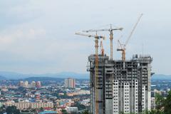 Construction cranes working on building - stock photo