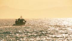 Fishing boat on the horizon crosses the sea at sunset,long shot. - stock footage