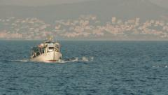 Fishing boat crosses the sea at afternoon,long shot. - stock footage