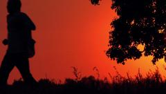 Silhouette of Man Running Through Countryside in Sunset - stock footage