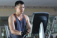 Exercising in the gym,Man walking on treadmill. - stock photo