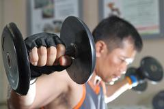 Muscular man working out with dumbbells - stock photo