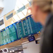 Female traveller checking flight departures board. - stock photo