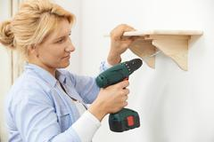 Woman Putting Up Wooden Shelf At Home Using Cordless Drill - stock photo