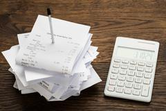 High Angle View Of Receipts With Calculator On Wooden Table Stock Photos