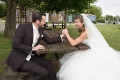 Stock Photo of Young happy newly wed couple  fighting in arm wrestling