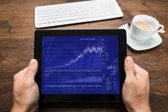 Close-up Of Person Hands With Digital Tablet Showing Graph At Desk - stock photo