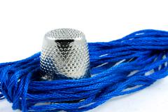 soft blue cotton thread and a thimble - stock photo