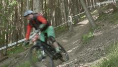 Two Mountain bikers racing downhill through tree's, Scotland Stock Footage