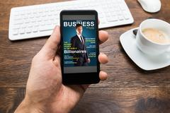 Close-up Of Person Hands With Mobile Phone Showing Business News Stock Photos