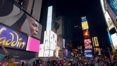 Commercial billboards and crowds on Times Square New York City at night Stock Footage