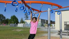 Cute Asian Girl With Face Paint On Playground Rings - stock footage