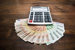 Close-up Of A Calculator Kept On Euro Banknotes On Desk - stock photo