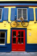 Bicycle on top of the entrance door near the window, in Quebec, Canada. - stock photo