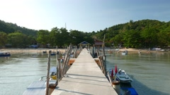 Move by long fisherman pier to canopy cover, walk into Stock Footage
