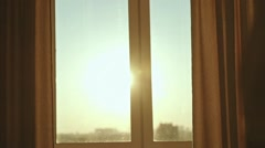 Young woman drinking coffee by the window during sunrise in her cozy home. - stock footage