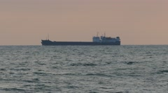 Cargo ship sailing from open sea on the sunset time. Arkistovideo