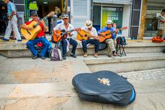 Unidentify indigenous men playing guitar in the commercial street plaza and Stock Photos