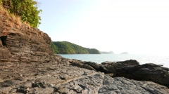Climb along unusual vulcanic rocky shore, layered black stones Stock Footage