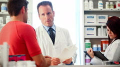 Stock Video Footage of Pharmacy: Pharmacist Asks Co-Worker For Advice With Prescription