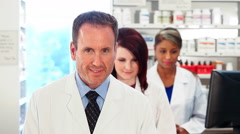 Pharmacy: Cheerful Male Pharmacist Leads Group Stock Footage