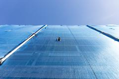 building with scaffolding draped in blue debris netting - stock photo