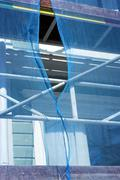 Scafflolding draped in blue debris netting with gap - stock photo