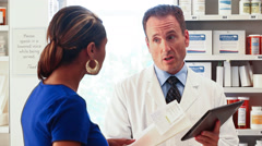 Pharmacy: Woman Seeks Advice And Instructions From Pharmacist Stock Footage
