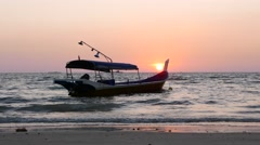 Fishing boat beach sunset, backlit, telephoto view, shallow water Stock Footage