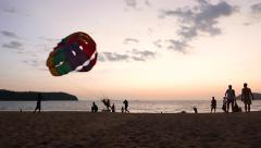 Parasailing landing silhouette view, tropical beach at sunset dusk Stock Footage
