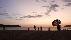 Evening beach silhouettes, parasail, parachute driven by motor boat rise up Stock Footage