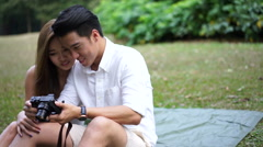Dolly footage of asian couple looking at their own pictures Stock Footage