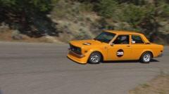 motorsports, hillclimb race, into hairpin, orange Datsun 510 - stock footage