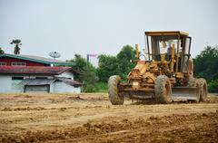 Motor grade Machine and people working at construction site Stock Photos