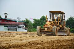 Motor grade Machine and people working at construction site - stock photo