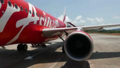 AirAsia plane livery, wing and engine view, FPV boarding by movable stairs Stock Footage