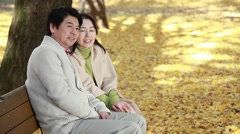 Japanese mature couple relaxing on a bench in a city park in Autumn Stock Footage