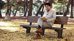 Japanese mature male reading a book on a bench in a city park in Autumn Stock Footage