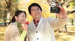 Japanese mature couple taking selfies in a city park in Autumn Stock Footage