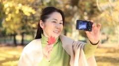 Japanese mature female taking selfies in a city park in Autumn Stock Footage