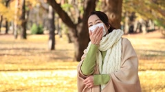 Japanese mature female wearing a mask feeling sick in a city park in Autumn - stock footage