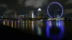 Singapore Skyline at Marina Bay at Night with Rotating Flyer and Reflection Stock Footage